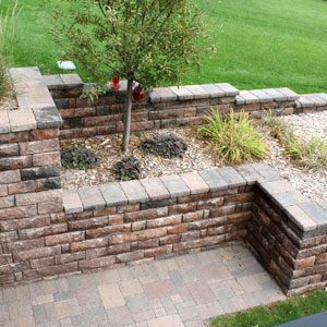 A variety of trees and bushes planted into a retaining wall made of bricks